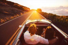 Paar fährt mit Cabrio in den Sonnenuntergang