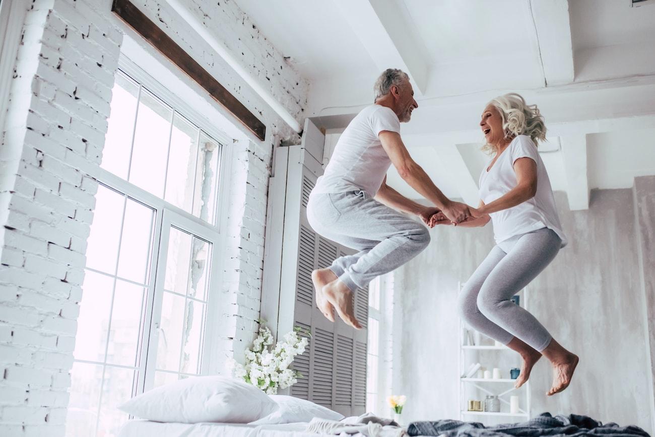 Altes Paar springt auf dem Bett