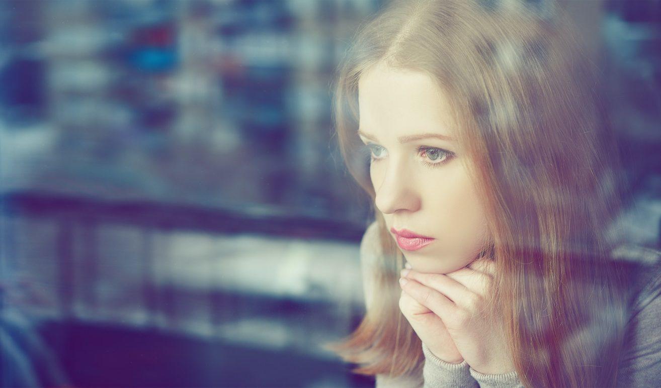 Frau einsam am Fenster